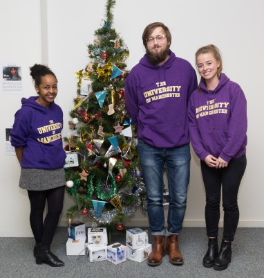 Our UoM Student Ambassadors standing with the IDDP Christmas tree: (left to right) Sarah, Jordan & Glesni